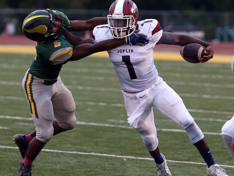 Joplin quarterback Jokiem Crawford fights off CJ Loveall of Parkview in Springfield on August 26, 2016.