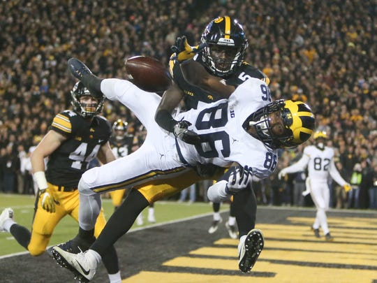 Michigan's Jehu Chesson is defended by Iowa's Manny