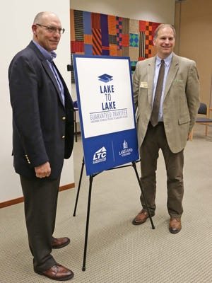 Lakeshore Technical College President Michael Lanser, left, and Lakeland College President Daniel Eck, pose for a photo by the logo for the new Lake to Lake educational program between the two educational systems Tuesday, Oct. 27, in Sheboygan.