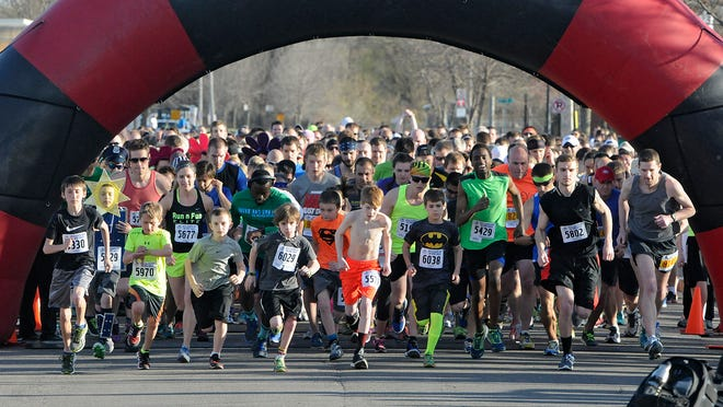 Competitors leave the starting line for the Earth Day 5K race Friday in St. Cloud.