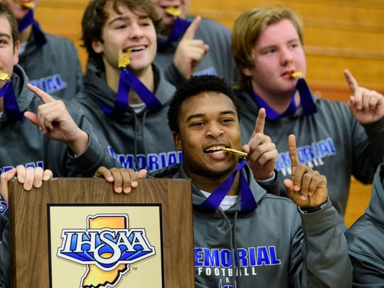 Memorial's Kenyon Ervin (21) poses for pictures with the other seniors on the football team after a celebratory pep rally held in their honor at Reitz Memorial High School in Evansville, Ind., Monday morning, Nov. 27, 2017. Ervin and the rest of the Memorial Tigers earned the first IHSAA 3A football state championship title in school history.