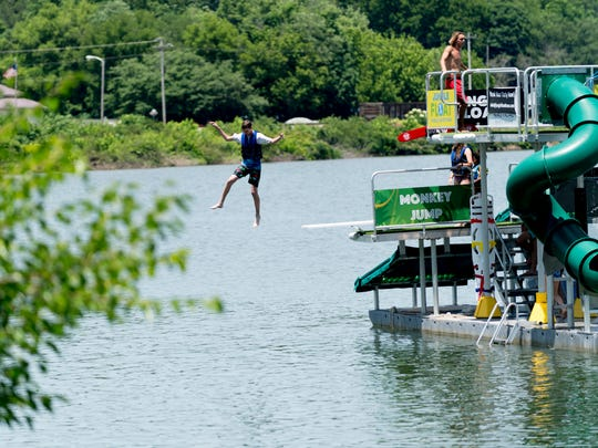 A kid jumps from the Jungle Float in Rocky Point Park in Farragut, Tennessee on Thursday, June 7, 2018. Jungle Float is a floating 35-foot water park featuring a rope swing, two launching trampoline platforms, a diving board, a high-jump platform, and a water slide.