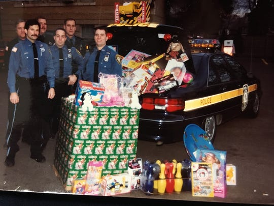 Clarke Osborn (far right) during the Suffern Police Department's early days of collecting gifts in the early 1990s.