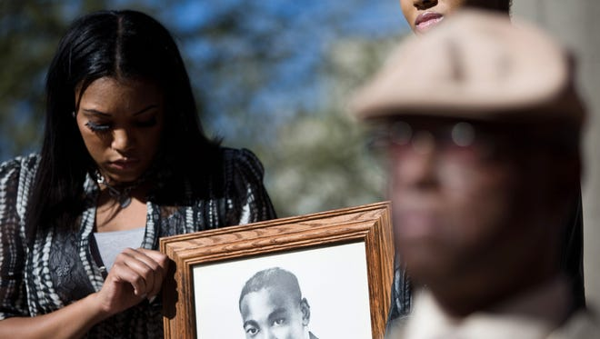 Rhyen Thompson, 21, left, with her sister Jai-Cea Gaston, 22, holds a photo of Martin Luther King Jr. as civil rights leaders hold a news conference Jan. 21, 2014, in Phoenix to demand that Arizona State University expel the Tau Kappa Epsilon fraternity from campus.