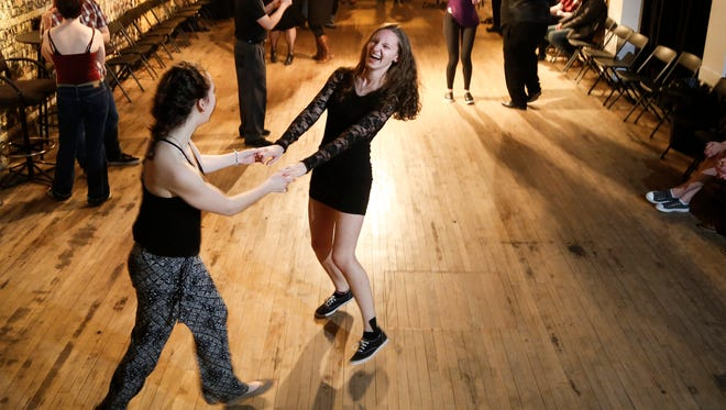 Ariel Fox, 22, left, of Rochester, and Courtney Kent, 19, of Grand Rapids dance Friday, April 21, 2017, after Sugar House Blues dance instruction at the AA Creative Corridor in REO Town.