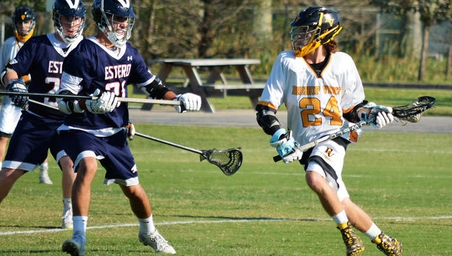Bishop Verot senior Tagg Toscano, right, looks to attack against Estero in a spring lacrosse game.