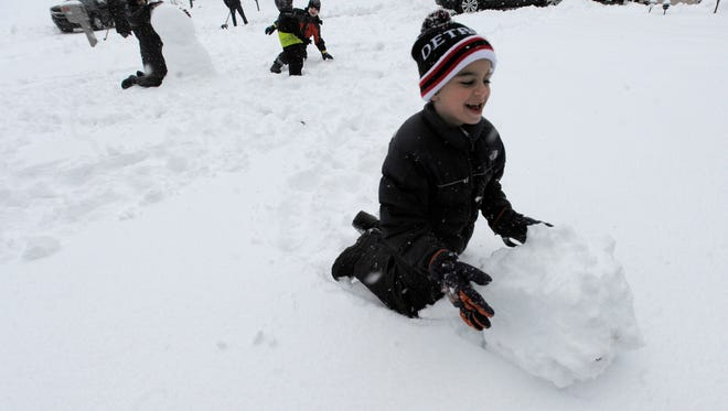 Adam Zetouna, 6, of West Bloomfied, rolls up the head of a snowman with his siblings, Megan, 13, Gabriel, 11, and Noah 2, in front of their West Bloomfield home.