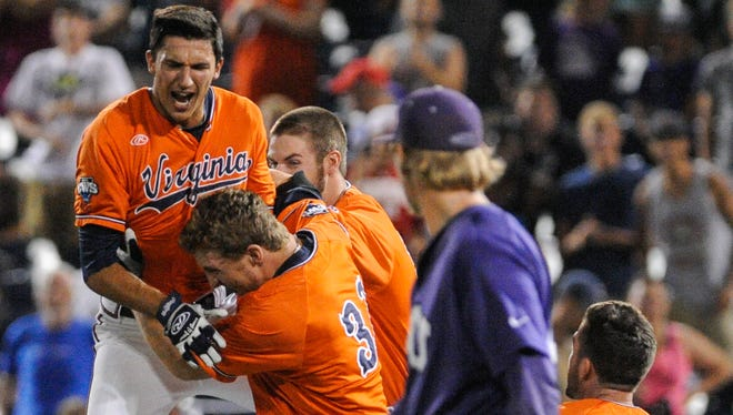 Virginia shortstop Daniel Pinero, left, celebrates with Thomas Woodruff (37) and their teammates after beating Texas Christian 3-2 in 15 innings Tuesday at the College World Series in Omaha, Neb.