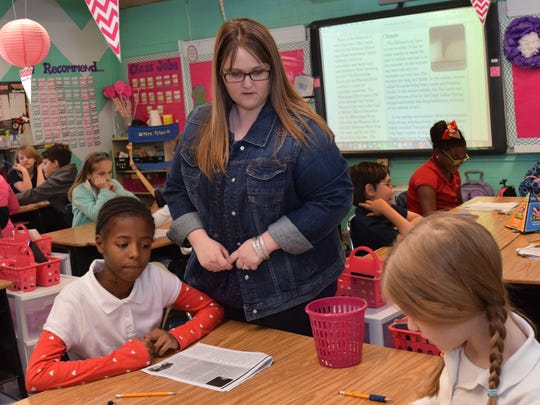 Phoenix Magnet Elementary School fourth-grade teacher Jennifer Tyler instructs students Elizabeth Drell (left) and Ada Shoup during a class exercise Tuesday.