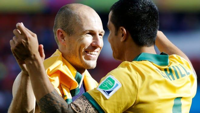 Netherlands' Arjen Robben, left, hugs Australia's Tim Cahill following the team's match Wednesday at the Estadio Beira-Rio in Porto Alegre, Brazil.