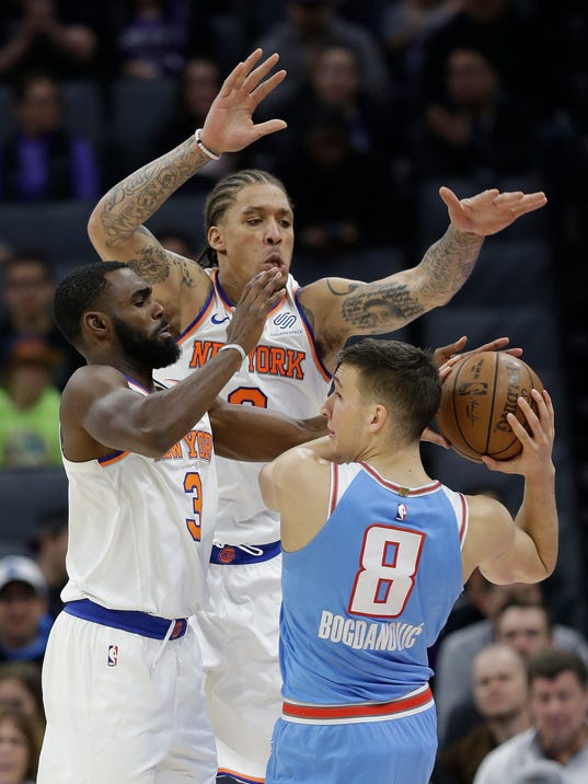 Sacramento Kings guard Bogdan Bogdanovic, right, is double-teamed by New York Knicks' Tim Hardaway Jr., left, and Michael Beasley during the first half of an NBA basketball game, Sunday, March 4, 2018, in Sacramento, Calif. (AP Photo/Rich Pedroncelli)