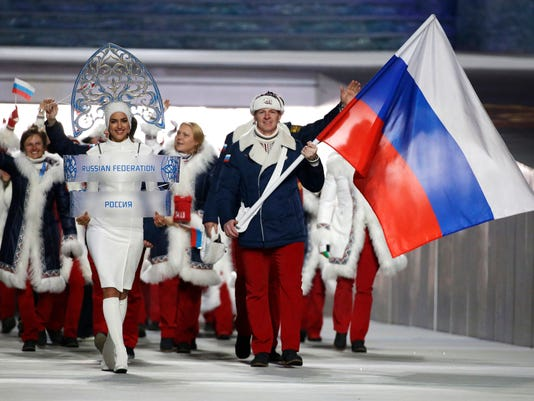 FILE - In this Feb. 7, 2014 file photo Alexander Zubkov of Russia carries the national flag as he leads the team during the opening ceremony of the 2014 Winter Olympics in Sochi, Russia. When the International Olympic Committee board prepares to vote Tuesday, Dec. 5, 2017 on whether to ban Russia from February's Winter Olympics, its members will decide the fate of numerous medals yet to be won. (AP Photo/Mark Humphrey, file)