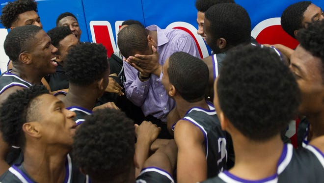 Cane Ridge players celebrate with their head coach Marlin Simms after their overtime win in the TSSAA district 12-AAA basketball championship over Antioch at McGavock High School Saturday, Feb. 18, 2017 in Nashville, Tenn.