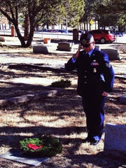 A lone soldier pays tribute at the grave site of a local veteran at the 2015 Wreaths Across America veterans tribute.