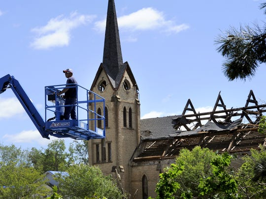 A worker on a lift in Portland  with the heavily damaged First Baptist Church behind as the cleanup continued on June 23, 2015 after the previous day's tornado.