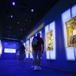 "Visitors look over display cases at the ""Forever Remembered"" exhibit at the Kennedy Space Center Visitor Complex in Cape Canaveral, Fla."