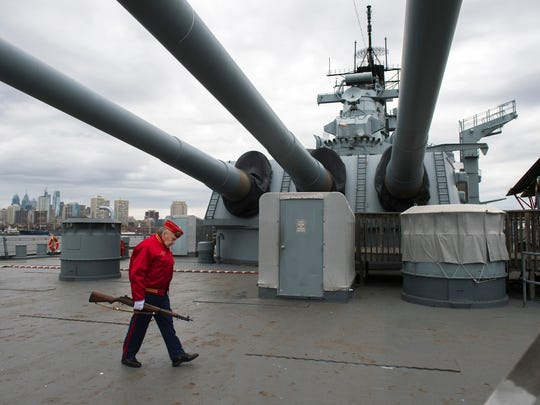 John Heath of the Marine Corps League carries his rifle aboard the USS New Jersey after a 21-gun salute honoring the 76th anniversary of the attack on Pearl Harbor Tuesday, Dec. 5, 2017 in Camden, New Jersey.