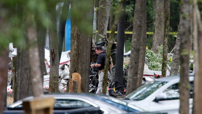 Tuscaloosa County Sheriff's Department Lt. Kip Hart walks through the site of a plane crash, Aug. 15, 2016, near Tuscaloosa Regional Airport in Tuscaloosa, Ala. The Aug. 14th crash killed three married Mississippi couples.(Gary Cosby Jr./The Tuscaloosa News via AP)