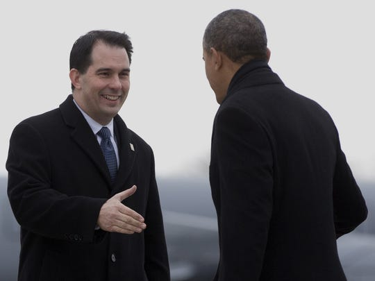 President Barack Obama was greeted by Wisconsin Gov. Scott Walker on a visit to Milwaukee on Thursday, Jan. 30, 2014. Walker won't greet Obama when he returns Saturday.