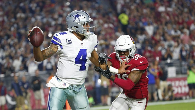 Dallas Cowboys quarterback Dak Prescott(4) escapes pressure from Arizona Cardinals safety Budda Baker (36) during the third quarter of Monday Night Football at University of Phoenix Stadium in Glendale, Ariz. September 25, 2017.