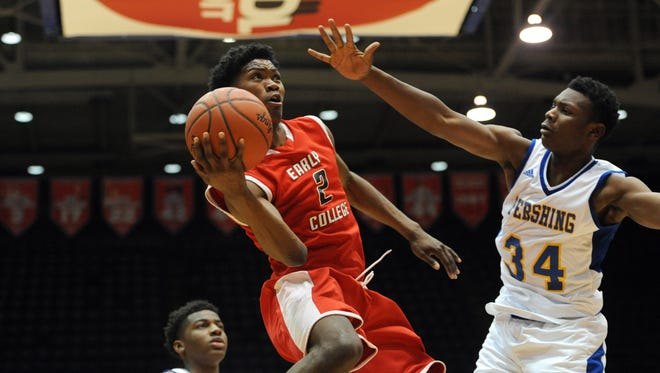 Detroit Edison guard Gary Solomon, left, goes up for a shot past Detroit Pershing forward Marquan Ross during the fourth quarter of Friday's PSL title game at Calihan Hall.