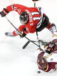 Ryan Poehling (11) of St. Cloud State and Jared Thomas