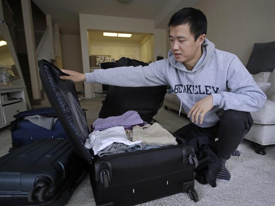 """In this Monday, Feb. 4, 2019, photo, Leo Wang packs a suitcase at his home in San Jose, Calif. Wang has found himself trapped in an obstacle course regarding H-1B work visas for foreigners. His visa denied and his days in the United States numbered, Wang is looking for work outside the country. """"I still believe in the American dream,"""" he says. """"It's just that I personally have to pursue it somewhere else."""""""