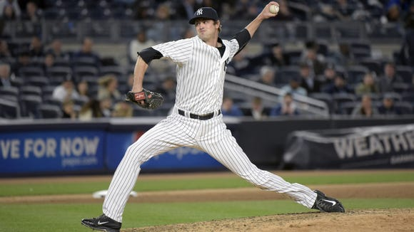 New York Yankees pitcher Andrew Miller delivers the ball to the Oakland Athletics  during the ninth inning of a baseball game Tuesday at Yankee Stadium in New York.