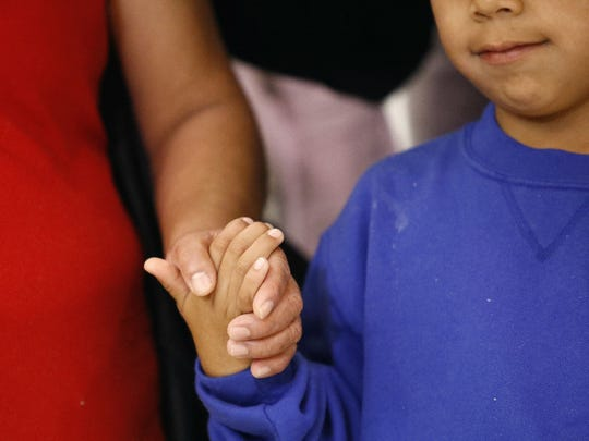 A mother and son from Guatemala hold hands during a