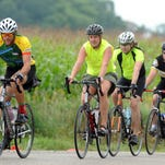 A group of bicyclists ride past the cornfields on DeWitt Road as DALMAC riders began their journey in 2014 after leaving East Lansing.