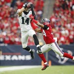 Eagles wide receiver Riley Cooper (14) catches a pass over Houston Texans cornerback A.J. Bouye (34) during a game from last November. Cooper is the veteran of the Eagles' WR corps.