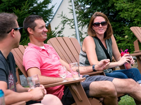 From left, Ryan Hill of Altoona, Pennsylvania, and Kevin and Angela Cloutier of Pittsburgh lounge outdoors at Three Brothers Wineries and Estates in Geneva on July 15.