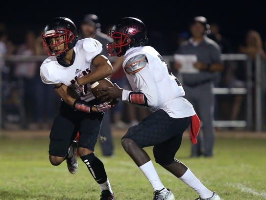 West Oso Bears quarterback Clyde Coleman (right) hands