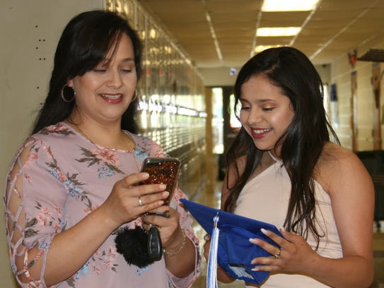Cotter graduate Hannia Garay (right) shares a special moment as she prepares for the graduation ceremony.