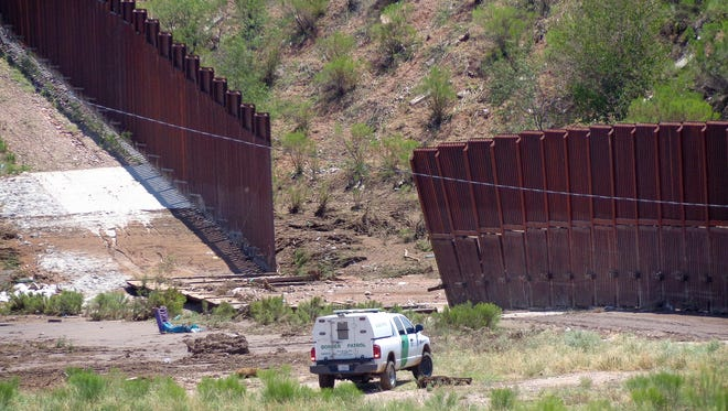 A border patrol vehicle stands guard at a section of collapsed fence near Nogales, Ariz., Sunday, July 27, 2014, after storms knocked down a chunk of the metal border fence that divides Mexico and the U.S.