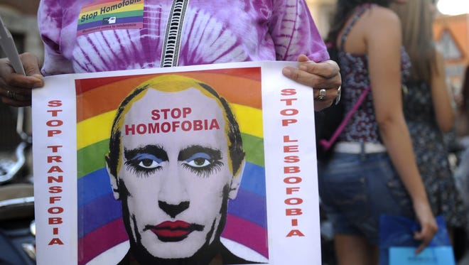 A demonstrator holds a poster depicting Russian President Vladimir Putin with make-up as he protests against homophobia and repression against gays in Russia, outside the Ministry of Foreign Affairs and Cooperation in Madrid on  Tuesday.  About 300 gay rights activists rallied in Madrid.