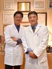 Dr. Greigh I. Hirata, right, poses for a photo with Dr. Thomas Shieh, left, at Dr. Shieh's Clinic in Tamuning on Sept. 6.