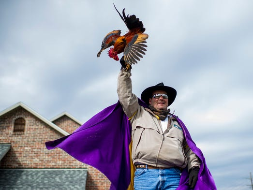 Gary Douget raises a rooster above his head before