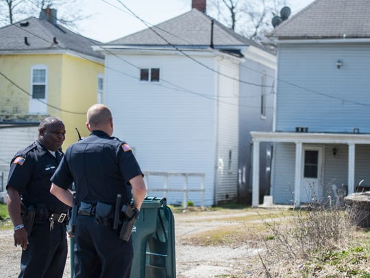 Richmond police officers stand outside a home in the 100 block of N. 14th St., Richmond, as they wait for a search warrant for the property on Wednesday, April 11, 2018.