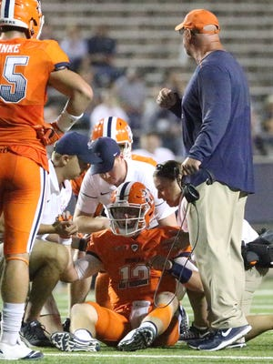 Coach Sean Kugler goes onto the field to check on quarterback Ryan Metz, 12, after he was shaken following a quarterback keeper play against Old Dominion on Saturday in the Sun Bowl.