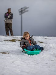A family uses the hill at Canyon View High for sledding,