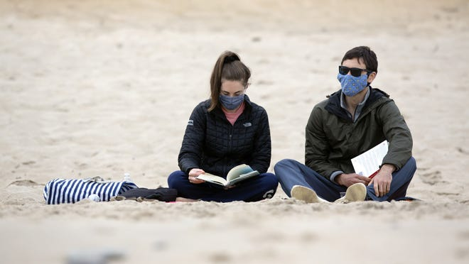 FILE - Amanda Pensack, left, and Derek Engelking, of Weymouth, Mass., sit on Marconi Beach, part of Cape Cod National Seashore, Monday, May 25, 2020, in Wellfleet, Mass.