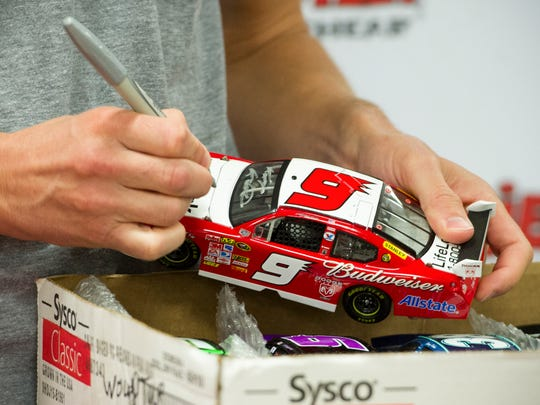 NASCAR driver Kasey Kahne signs an autograph for a fan during the grand opening of Ollie's Bargain Outlet in Evansville, Wednesday, Sept. 21, 2016.