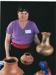 "Taos Pueblo potter Pam Lujan-Hauer poses with her award-winning ""Six Direction Water Jar"" during a show at the University of Arizona in Tucson."