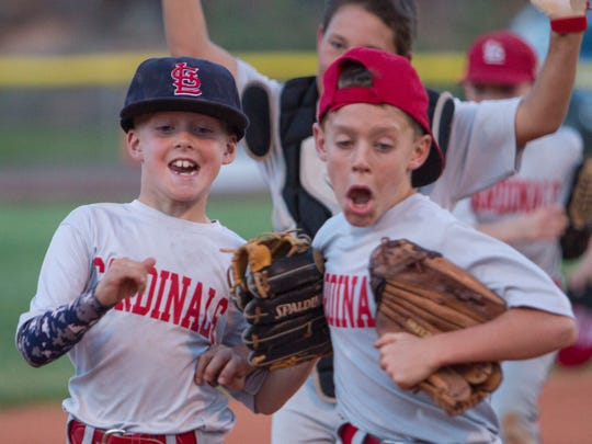 The little league Cardinals celebrate a comeback win against the Giants Tuesday, May 26, 2015.