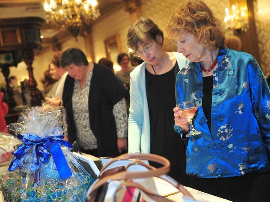 Soup kitchen supporters Susan Oxman of Morristown and Nancy Bailin of Mendham look over the silent auction items.