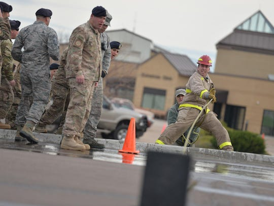 Airmen compete in the annual fire muster for Fire Prevention