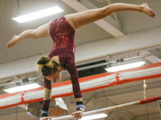 Hillsborough's Sam Ringel performs on the uneven bars