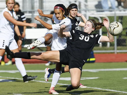 East Brunswick's Alyna Negron clears the ball from