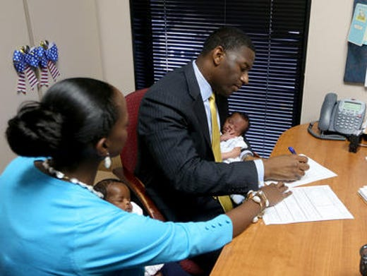 Tallahassee City Commissioner Andrew Gillum holds his twin son, Jackson, while handing over his paperwork to run for the mayor of Tallahassee. His wife R. Jai holds daughter Caroline.